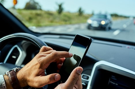 Closeup of a motorist texting while driving